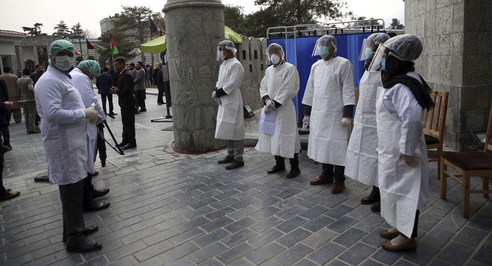 العاملون الصحيون الأفغان ينتظرون لقياس درجة حرارة الضيوف للتحقق من وجود فيروسات تاجية عند بوابة دخول القصر الرئاسي خلال حفل تنصيب الرئيس الأفغاني أشرف غني في كابول