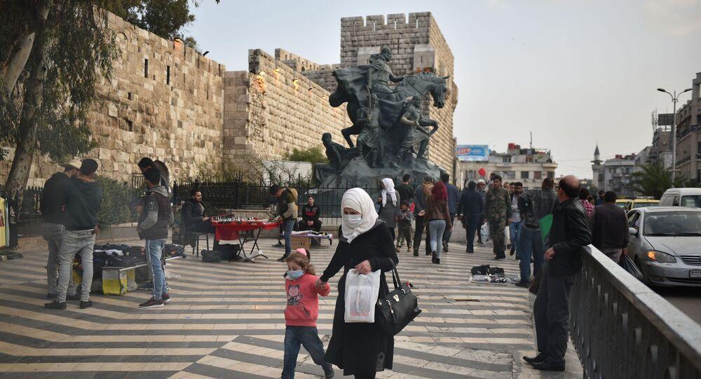سوريين يرتدون الأقنعة الواقية في دمشق خوفا من كورونا
