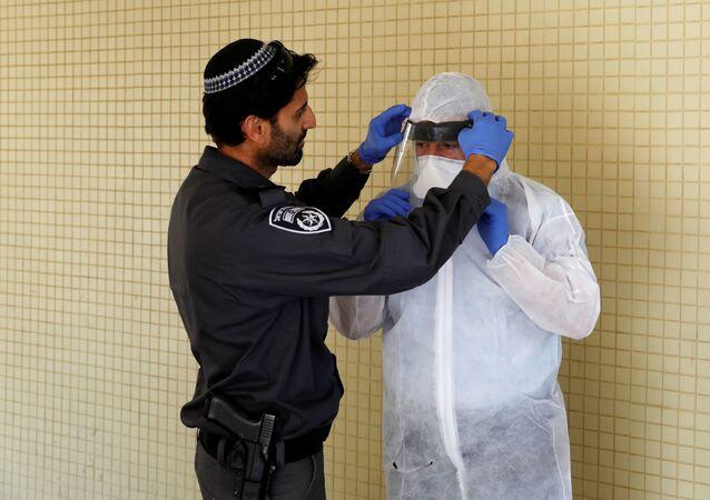 ضابط في الشرطة الإسرائيلية يساعد مفتش في وزارة الصحة على ارتداء معدات واقية قبل أن يصعد إلى شقة شخص في الحجر الصحي