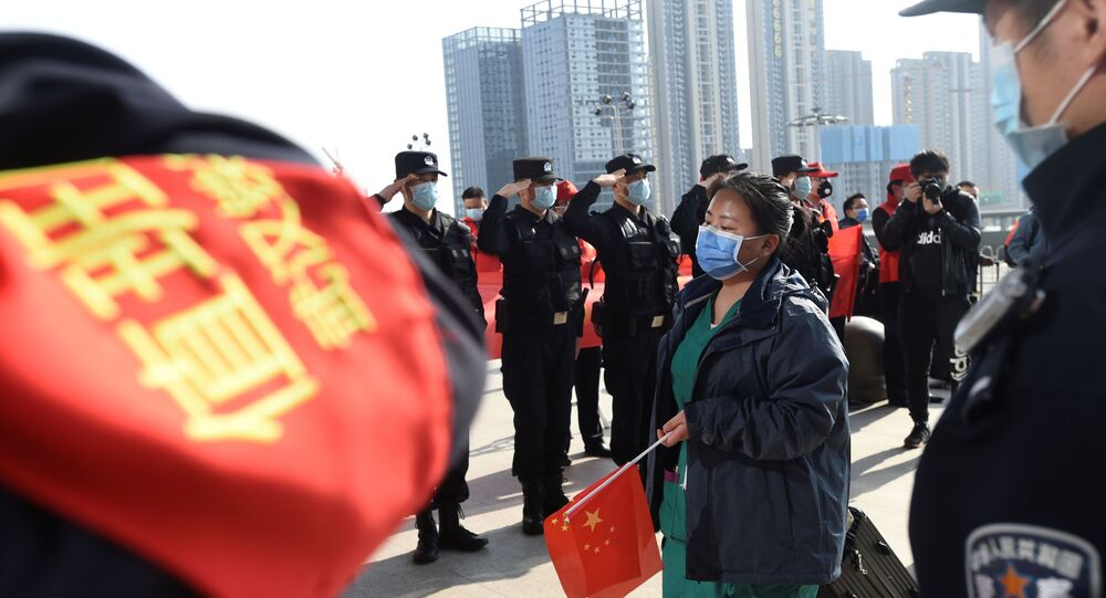 الشرطة الصينية تقدم التحية العسكرية للعاملين بالجهاز الطبي في منطقة ووهان مركز تفشي فيروس كورونا.