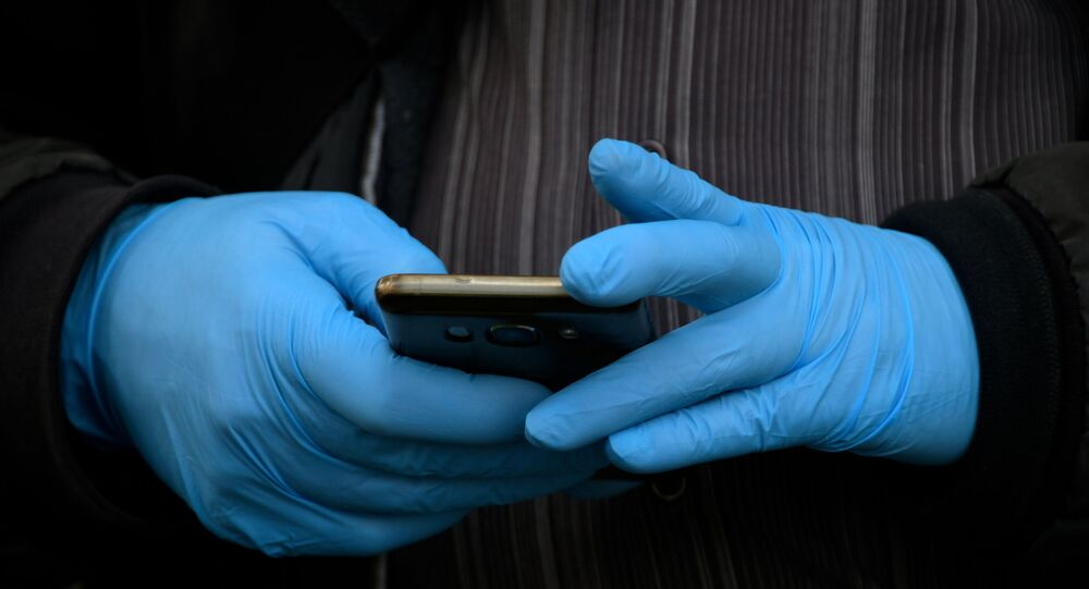 رجل يرتدي قفازات واقية بينما يمسك هاتفه الذكي