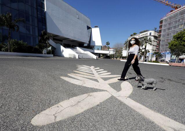 امرأة ترتدي كمامة طبية بينما تسير بصحبة كلبها على السعفة الذهبية رمز مهرجان كان السينمائي الدولي