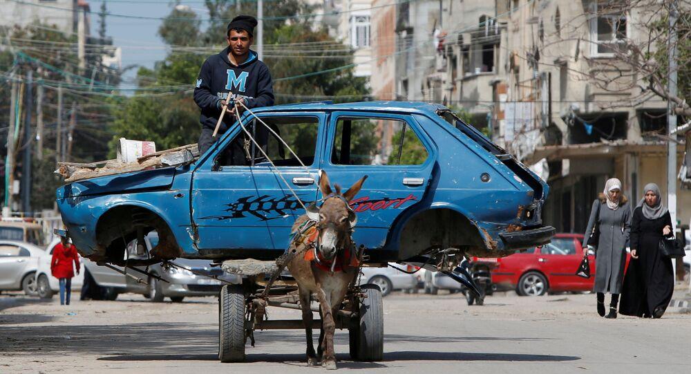 فلسطيني يركب عربة يجرها الحمار تنقل سيارة قديمة إلى ساحة للخردة، في مدينة غزة، 15 مارس، 2020.