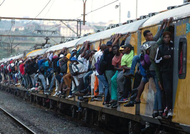 ركاب يمسكون بالقطار ركاب مكتظ في سويتو، جنوب أفريقيا، 16 مارس 2020.
