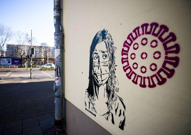 رسم غرافيتي لفتاة ترتدي قناعا واقيا بجوار صورة توضيحية لفيروس كورونا المستجد، برلين، ألمانيا 14 فبراير 2020