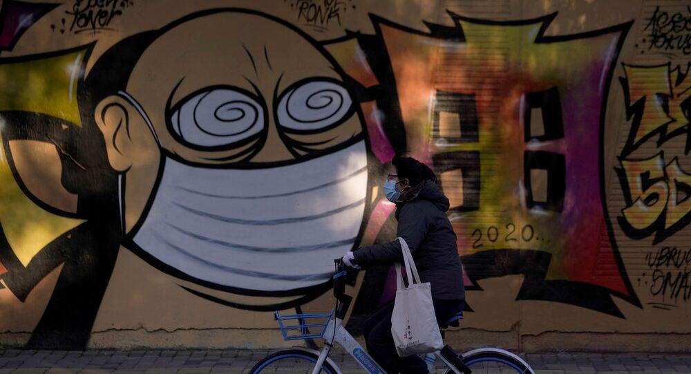 امرأة ترتدي قناعا واقيا تسير على خلفية رسم غرافيتي لشخص يرتدي قناعا واقيا، شنغهاي، الصين 17 فبراير 2020