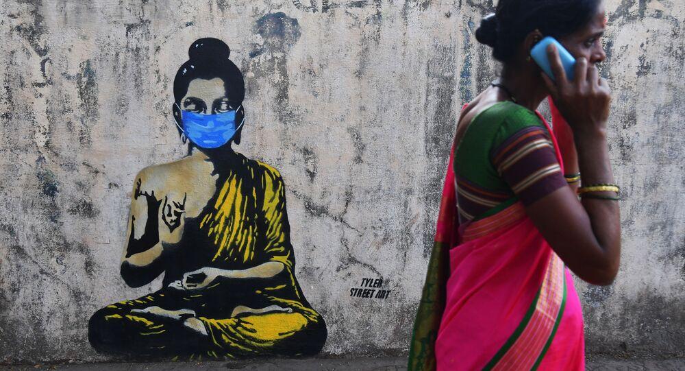 امرأة تسير على خلفية رسم غرافيتي لبوذا يرتدي قناعا واقيا، مومباي، الهند 16 مارس 2020