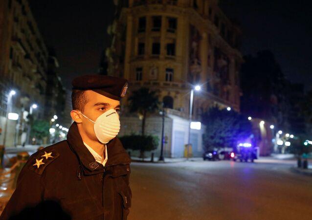 ضابط مصري يرتدي كمامة واقية من فيروس كورونا في أثناء تنفيذ حظر التجوال في البلاد