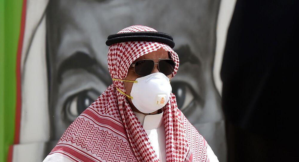 مواطن سعودي يرتدي قناعًا وقائيًا كإجراء احترازي ضد فايروس كورونا، يسير أمام لوحة جدارية تظهر وجه الملك سلمان بن عبد العزيز ، في العاصمة الرياض ، 15 مارس 2020.