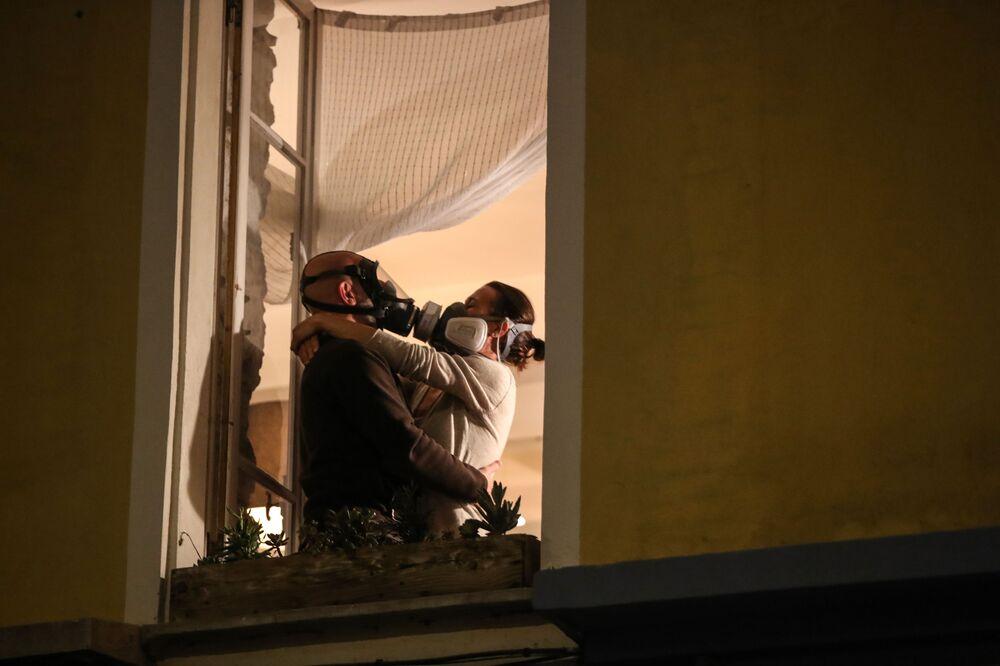 رجل وامرأة يرتديان أقنعة غاز يحتضنان على نافذتهما خلال فعالية التصفيق في الساعة الثامنة يوميا، لدعم العاملين في المجال الطبي، في مدينة الريفييرا الفرنسية في نيس، في 24 مارس 2020