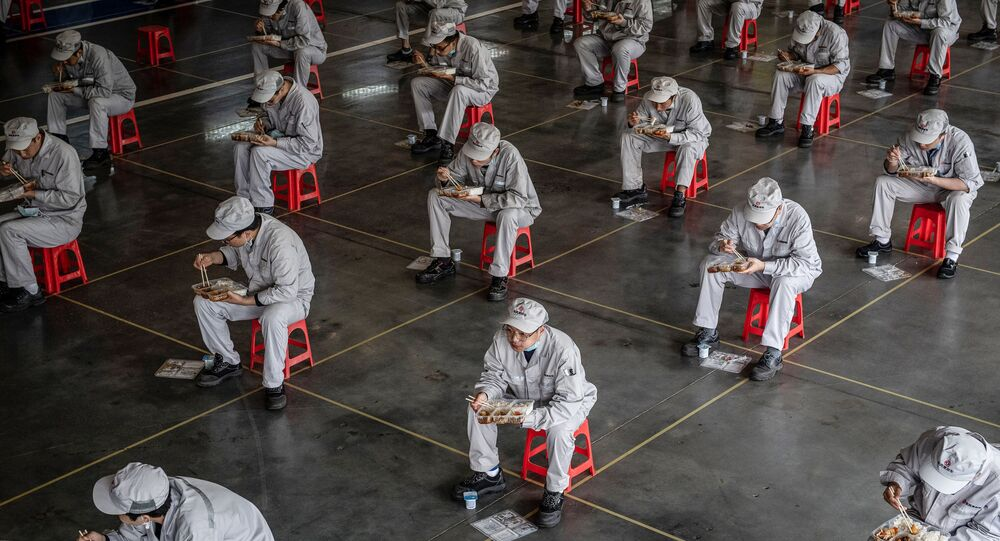 التقطت الصورة في 23 مارس 2020 ، الموظفون يتناولون الطعام أثناء استراحة الغداء في مصنع للسيارات Dongfeng Honda في مدينة ووهان، وسط الصين. - يُسمح الآن لأهالي المنطقة (بؤرة تفشي كورونا) في وسط الصين، لأول مرة  بالعودة إلى العمل وإعادة تشغيل وسائل النقل العام، حيث تعود بعض الأمور الطبيعية ببطء بعد فرض الحجر الصحي المتشدد لمدة شهرين.