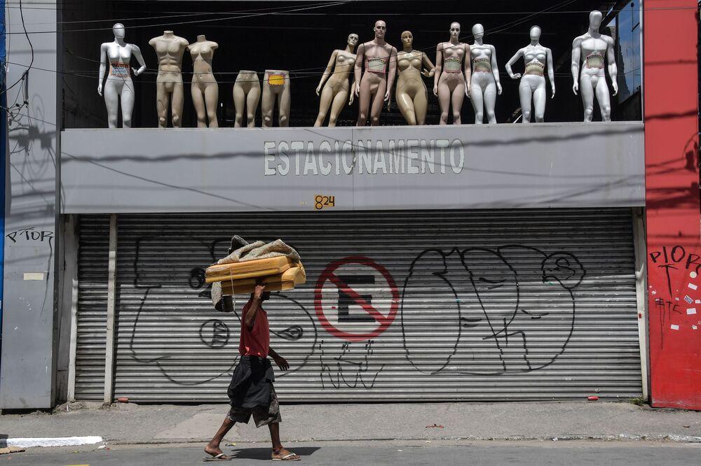 مشرد يسير أمام محل مغلق وسط مدينة ساو باولو في البرازيل، بعد أن أصدرت حكومة المدينة قرارًا بإغلاق المتاجر ومواقف السيارات كإجراء وقائي ضد انتشار فيروس كوروناالجديد في 24 مارس 2020