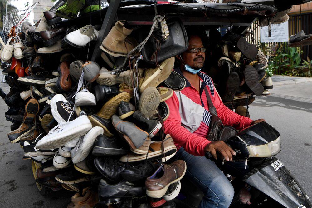 رجل يركب عربة محملة بأحذية مستعملة للبيع على طول شارع في بنوم بنه، كمبوديا في 24 مارس 2020