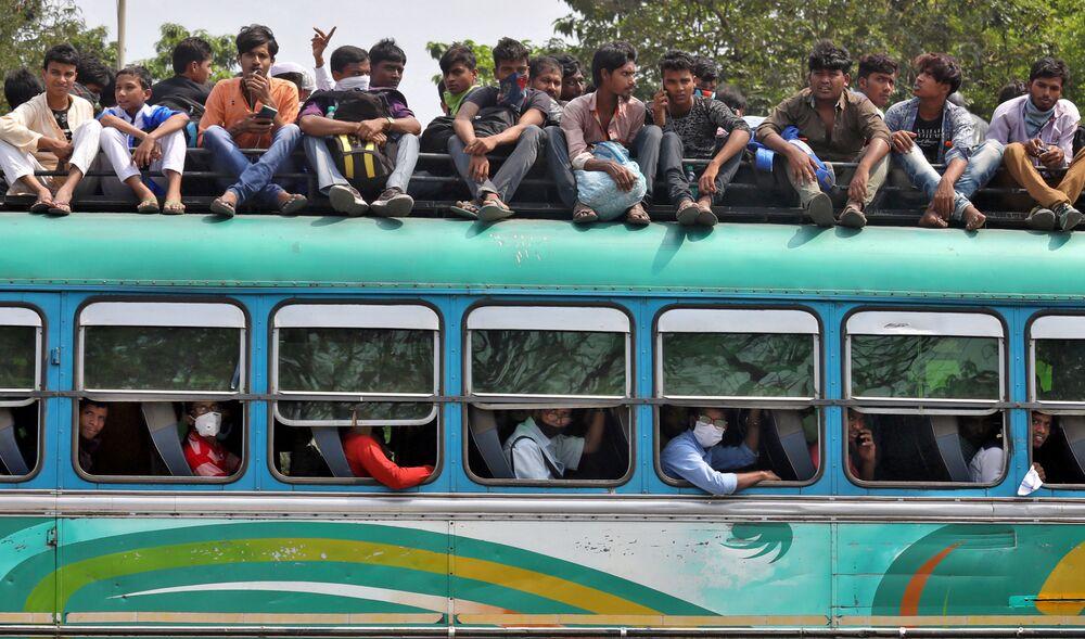 يعود الناس في حافلة مزدحمة إلى مدنهم وقراهم قبل بدء تنفيذ حظر التجول من قبل حكومة ولاية البنغال الغربية للحد من انتشار كوفيد-١٩ (كورونا)، في كلكتا، الهند 23 مارس 2020