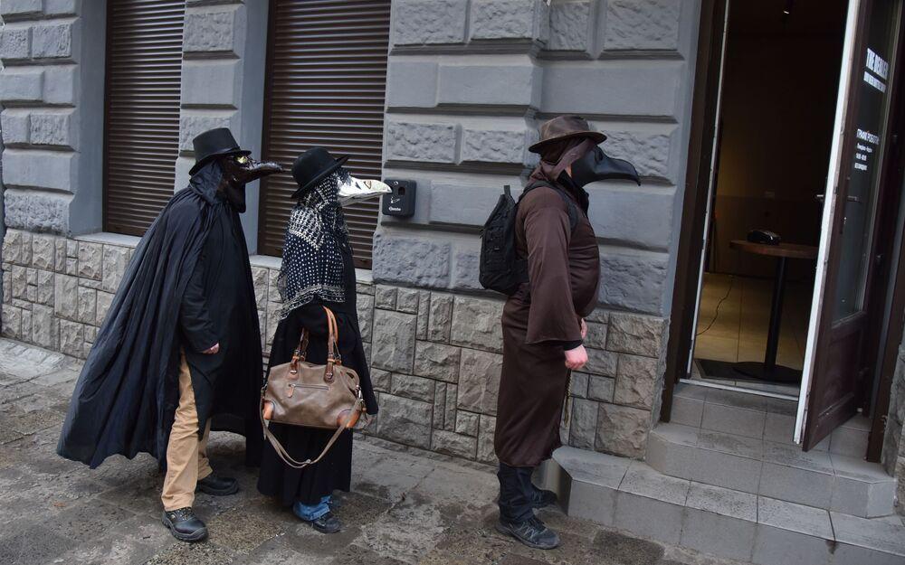أشخاص يرتدون أقنعة طبيب الطاعون في لفيف وسط تفشي مرض فيروس التاجي كورونا، أوكرانيا 22 مارس 2020