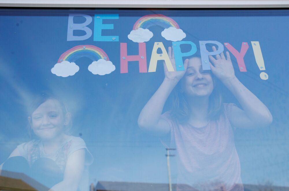 الفتاتان صوفي وإميلي وارد، خلف زجاد نافذتهما عليها رسالة كن سعيدا! في سانت هيلينز ، مع استمرار انتشار مرض فيروس التاجي (COVID-19). سانت هيلينز، بريطانيا، 25 مارس 2020