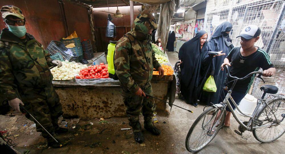 ضابط الدفاع المدني العراقي يقوم بتطهير الأماكن التجارية في ضواحي بغداد، في ظل انتشار فيروس كورونا في العراق 28 مارس 2020