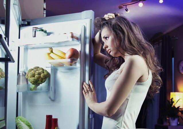 امرأة تقف إلى جانب الثلاجة