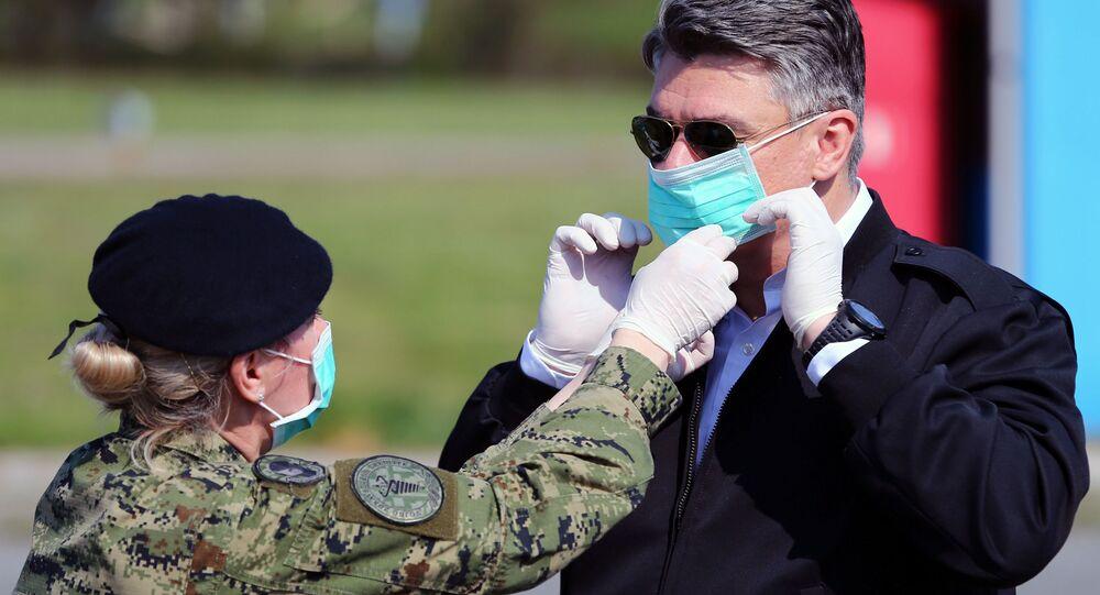 جندي يساعد الرئيس الكرواتي زوران ميلانوفيتش على ارتداء قناع للوجه قبيل زيارته الخيام التي تم إنشاءها لمرضى الفيروس التاجي (COVID-19) في مستشفى دوبرافا في زغرب، كرواتيا 21 مارس 2020.