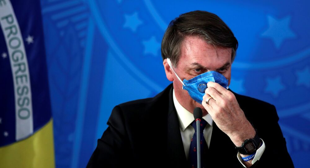 الرئيس البرازيلي جايير بولسونارو يعدل قناع وجهه أثناء بيان صحفي حول تفشي مرض فيروس كورونا (COVID-19) في البرازيل ، 20 مارس 2020