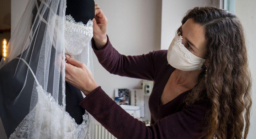 تقوم مصممة فساتين الزفاف وملابس السهرة، فريدريك جورزيغ، بتعديل عارضة أزياء ترتدي فستان زفاف وقناع واقٍ مطابق له، في متجرها شيتون في برلين، 31 مارس 2020، حيث تستمر أعداد ألمانيا محاربة جائحة فيروس Covid-19 المصابين بفيروس كورونا بالتزايد. - نظرًا لإلغاء جميع حفلات الزفاف والمناسبات، تقوم مصممة الأزياء الألمانية بإنشاء أقنعة أزياء عصرية في ورشتها وبيعها في متجرها في منطقة شونبيرغ في برلين.