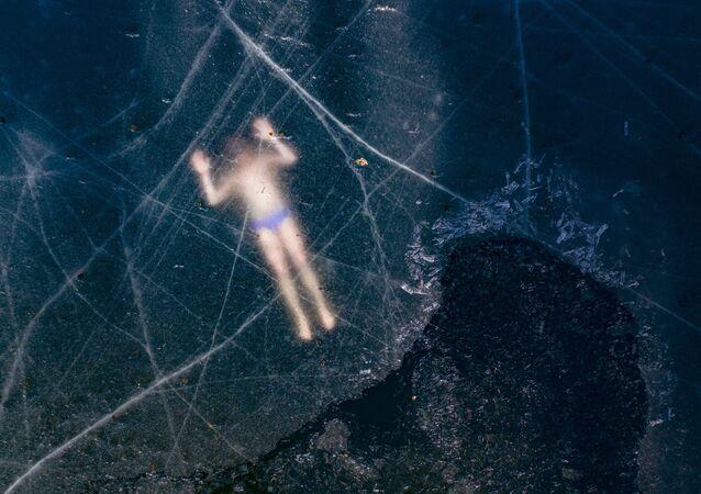 يُظهر الصورة الجوية الغطاس الحر الفنلندي كريستيان ماكي جوسيلا، 37 عامًا، وهو يسبح تحت جليد بحيرة متجمدة في 28 مارس 2020 بالقرب من فاسا، فنلندا 21 مارس 2020، حقق الرقم القياسي العالمي غير الرسمي لمسافة السباحة الحرة في زي السباحة بلغت طولها 101 متر، في بحيرة متجمدة في شمال فنلندا.