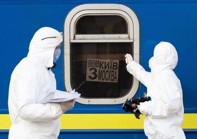 أطباء يرتدون زيا واقيا في قطار خاص رقم 906/905 كييف - موسكو - كييف، الذين وصلوا إلى محطة السكة الحديدية في مدينة كييف، لفحص المواطنين القادمين من موسكو بسبب فيروس كورونا،أوكرانيا،  29 مارس 2020