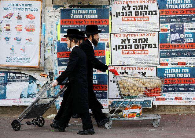 رجال اليهود الأرثوذوكس يدفعون عربات أثناء مرورهم على خلفية لوحات إعلانية تحث الناس على البقاء في منازلهم والالتزام بالاجراءات الحكومية لمنع  تفشي مرض فيروس التاجي (COVID-19) في أشدود، إسرائيل، 1 أبريل 2020.