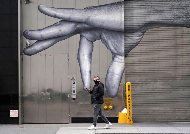 رجل يرتدي قناعاً واقياً يسير بجوار فن الشارع وسط انتشار الجائحة، فيروس كورونا في مدينة نيويورك، 05 أبريل 2020