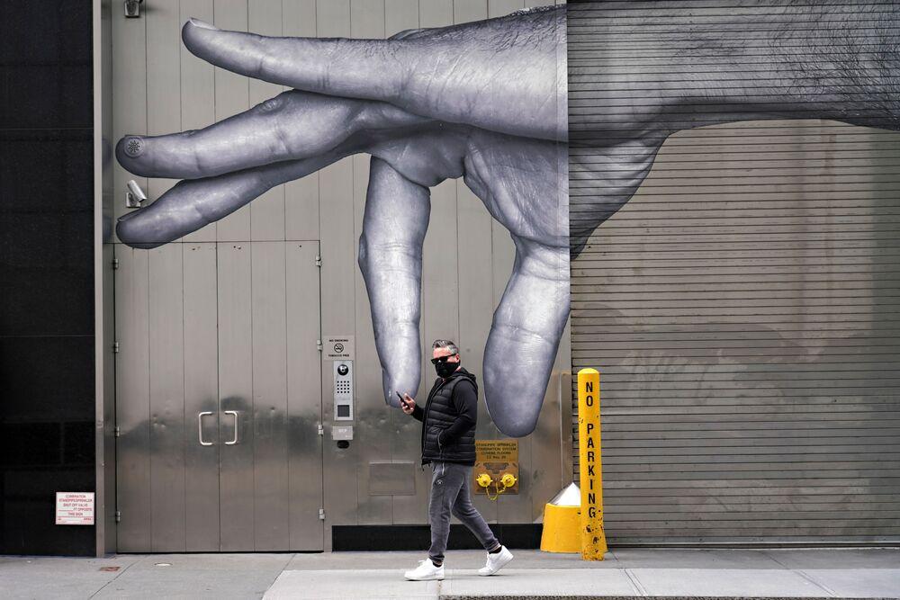 رجل يرتدي قناعاً واقياً يسير بجوار فن الشارع وسط انتشار الجائحة، فيروس كورونا في مدينة نيويورك، 5 أبريل 2020