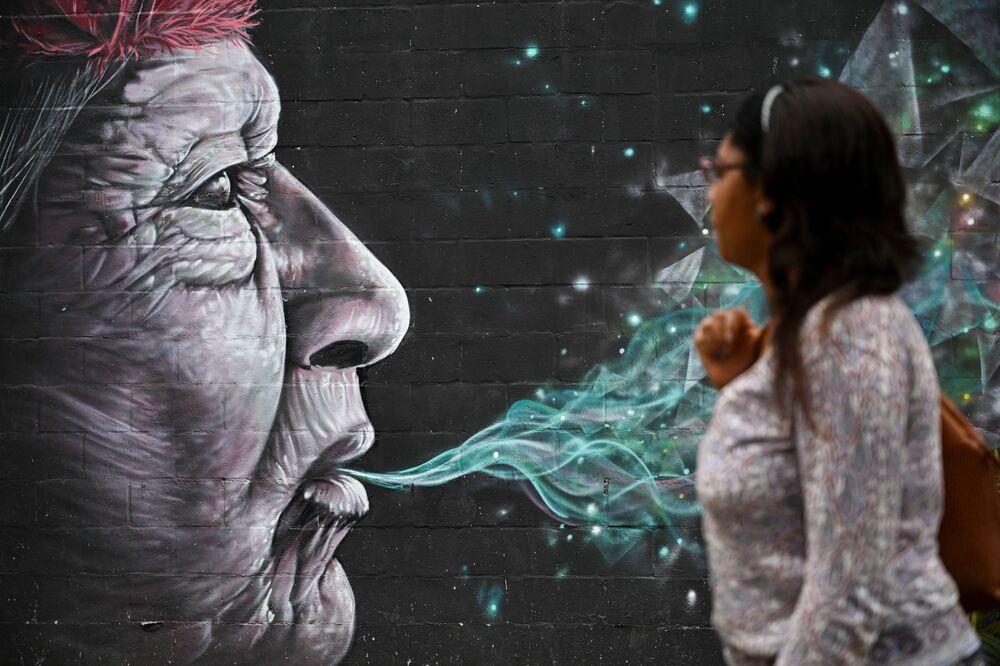 امرأة تسير على خلفية جدارية بمناسبة مهرجان غرافيكاليا (Graficalia) في مدينة كالي، كولومبيا 5 أبريل 2020