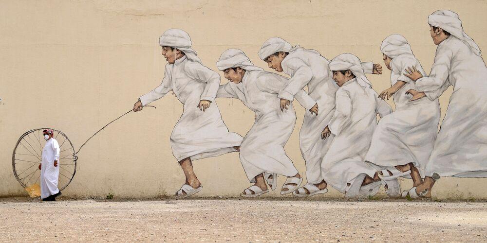 رجل إماراتي يرتدي قناع واقي يسير على خلفية جدارية في دبي، 28 مارس 2020