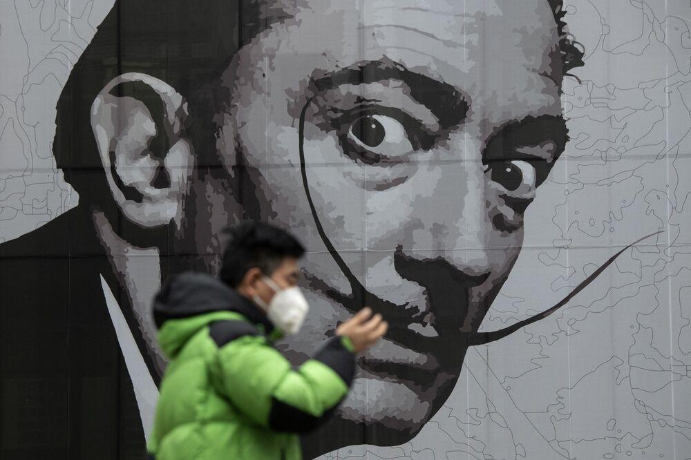 رجل يرتدي القناع الواقي يسير على خلفية جدارية في مركز تجاري في شنغهاي، الصين 7 فبراير 2020