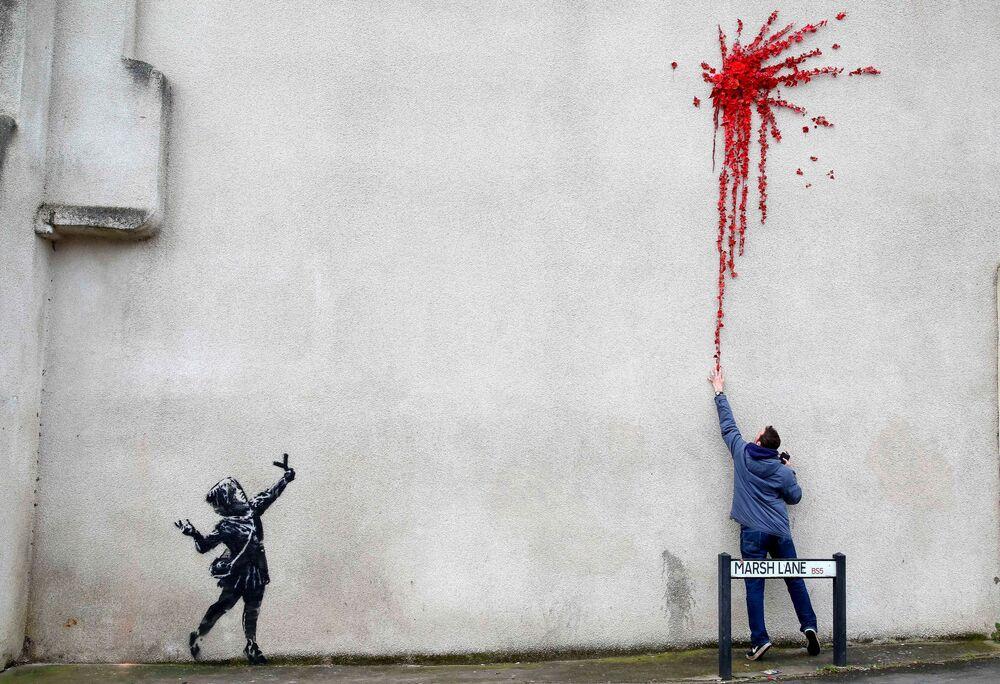 أحد المارة يقف على خلفية رسم غرافيتي لفنان الشارع الشهير بانكي، الرسم لفتاة صغيرة تطلق مقلاعًا من الزهور، على جدار مبنى في بريستول، بريطانيا 14 فبراير 2020.
