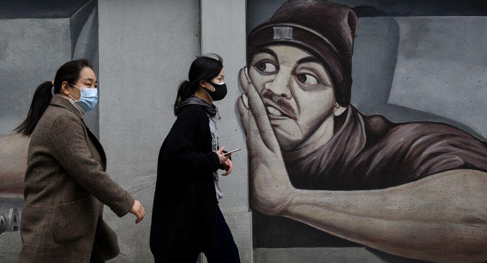 أشخاص يرتدون أقنعة واقية يمشون أمام جدارية على طول شارع في مدينة ووهان بمقاطعة هوبي وسط الصين، 2 أبريل 2020