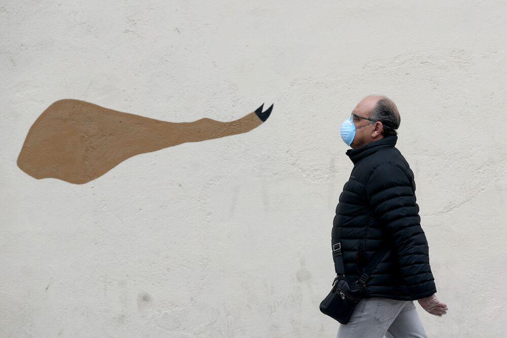 رجل يرتدي قناعا وقفازات واقية يسير على خلفية رسم غرافيتي لساق لحم خنزير الإيبيري (المشهورة في إسبانيا) أثناء الإغلاق التام، على خلفية انتشار مرض كوفيد-19 في مدريد، إسبانيا 6 أبريل 2020.
