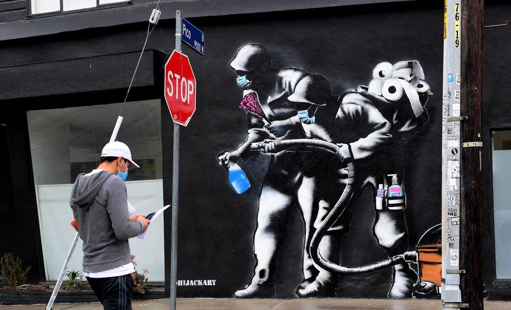 أحد المشاة يرتدي قناع واقي يسير أمام لوحة جدارية يدور موضوعها حول وضع العالم الحالي على خلفية تفشي كورونا، لفنان الشارع HIJACK الذي يصور ثنائياً مسلحًا بمطهر لليدين ولفافات من ورق المراحيض ومكنسة كهربائية في 6 أبريل 2020 في لوس أنجلوس، الولايات المتحدة