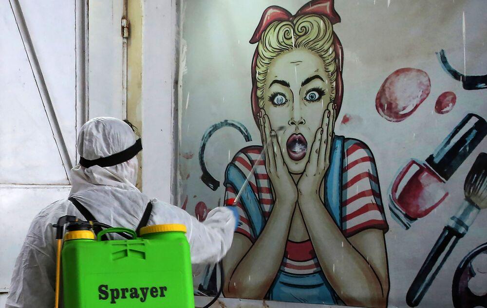 متطوع يقوم بتطهير متجر في حي البياع ببغداد، يوم 21 مارس 2020 ، كإجراء وقائي ضد انتشار الفيروس التاجي كوفيد-19، العراق