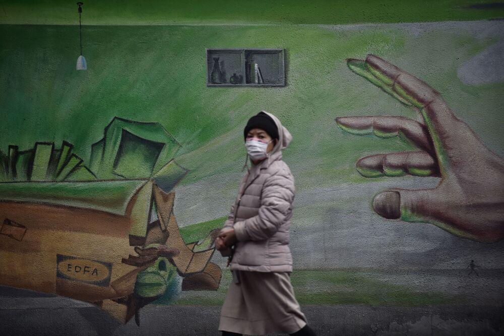 هذه الصورة التقطت في 28 فبراير 2020، حيث يظهر فيها مواطنة تسير على خلفية جدارية في مدينة ووهان في مقاطعة هوبي وسط الصين