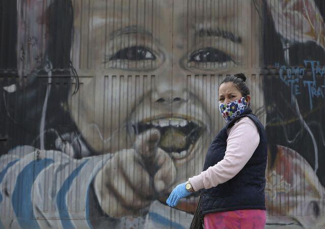امرأة ترتدي القناع الواقي وقفازات، تسير على خلفية لوحة جدارية في سواتشا، على مشارف مدينة بوغوتا في كولومبيا، 1 أبريل 2020 ، أثناء إغلاق تام على مستوى الدولة لأنها تسعى لمنع انتشار كوفيد-19.