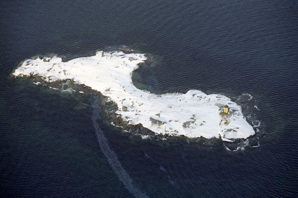 جزيرة بها منارة في بحر بارنتس خارج الدائرة القطبية الشمالية. صورة التقطت من مروحية أسطول الشمال الروسية