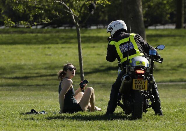 شرطي يطلب من فتاة مغادرة الحديقة، في ظل الإجراءات التقييدية خلال وباء الفيروس التاجي كورونا في لندن، بريطانيا 5 أبريل 2020