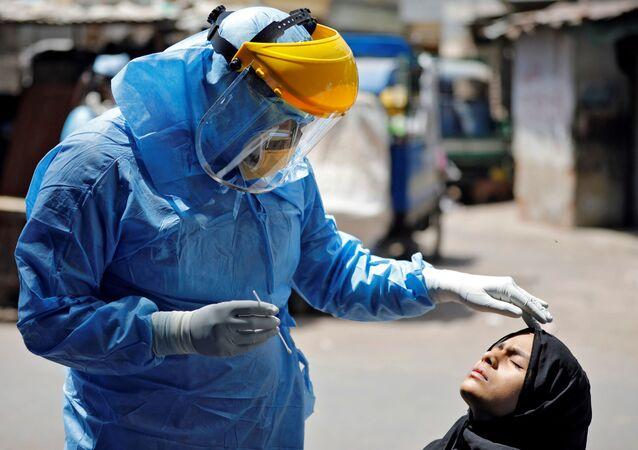 طبيب يرتدي بدلة واقية يفحص فتاة، تحاليل فيروس كورونا، في أحمد آباد، الهند 8 أبريل 2020