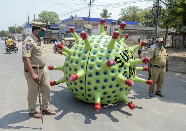يقوم ضباط الشرطة، سودهاكار يادار، بدورية بينما يقود المخترع (من الداخل) سيارته المصممة على شكل فيروس كورونا على طريق، بهدف حملة توعوية، أثناء الإغلاق الوطني التام فرضته الحكومة كإجراء وقائي لمنع تفشي مرض الفيروس التاجي كوفيد-19، في حيدر آباد، الهند 8 أبريل 2020.