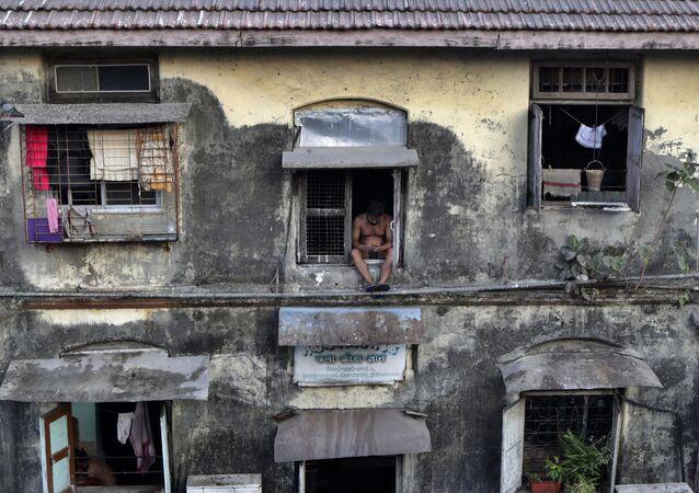 رجل يجلس على نافذة في شقته، أثناء الإغلاق التام لمنع انتشار الفيروس التاجي كورونا الجديد، في منطقة بارل في مومباي، الهند 5 أبريل 2020