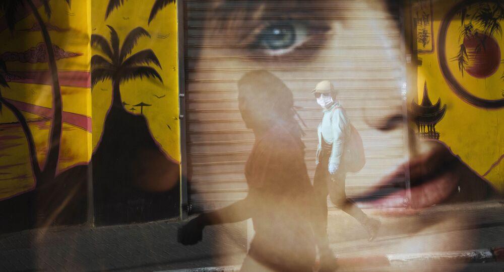 انعكاس امرأة مارة على زجاج محطة للحافلات، وهي ترتدي القناع الواقي، وسط مخاوف تفشي الفيروس التاجي  كورونا في تل أبيب، إسرائيل 6 أبريل 2020