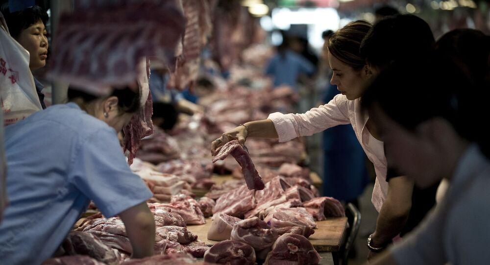عملاء يشترون لحم الخنزير بسوق في بكين