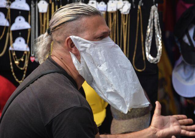بائع يرتدي قناعا للوقاية من عدوى فيروس كورونا في البرازيل 16 مارس 2020