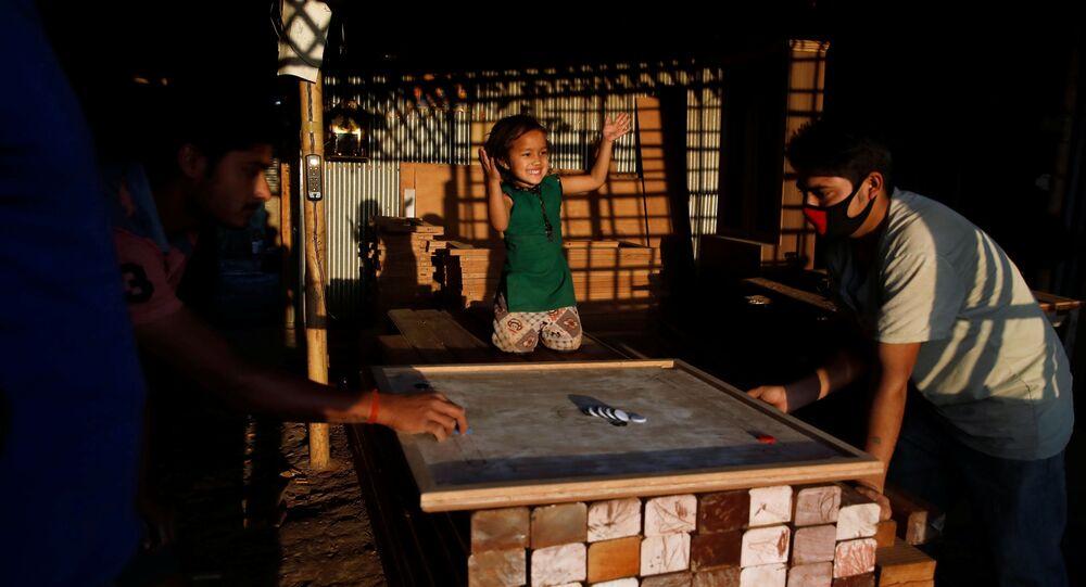 طفلة تهتف خلال لعب والدها على لوح الكيرم في ورشة أثاث خلال اليوم العاشر من الإغلاق الذي فرضته الحكومة بسبب كورونا في لاليتبور في نيبال