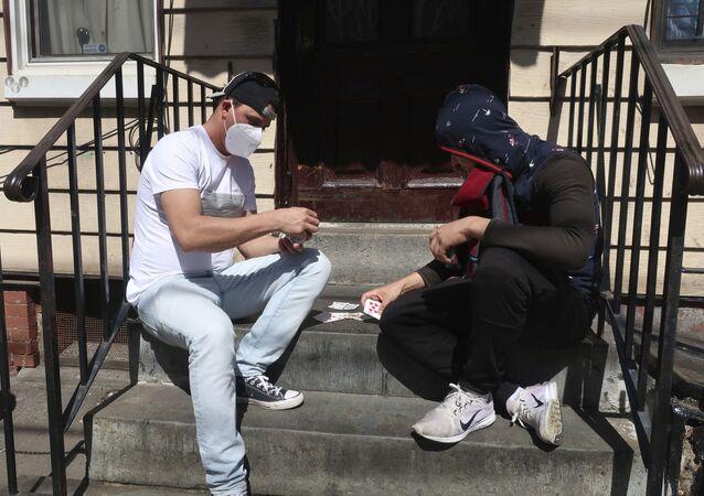 رجلان يرتديان أقنعة واقية يلعبان الورق أمام المنزل في بروكلين، نيويورك  2أبريل 2020